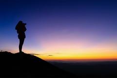 Silueta de la mujer que toma la fotografía en el top de la montaña y imagen de archivo
