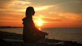 Silueta de la mujer sana hermosa joven que medita en la posici?n de loto por el mar en la puesta del sol El practicar de la mujer almacen de metraje de vídeo