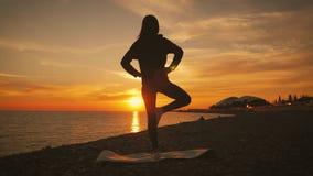 Silueta de la mujer sana hermosa joven que medita en la posici?n de loto por el mar en la puesta del sol El practicar de la mujer metrajes