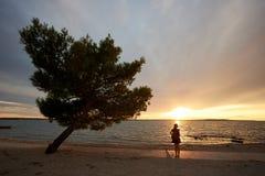 Silueta de la mujer solamente en el borde del agua, disfrutando de paisaje marino hermoso en la puesta del sol imágenes de archivo libres de regalías
