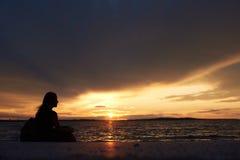 Silueta de la mujer solamente en el borde del agua, disfrutando de paisaje marino hermoso en la puesta del sol fotos de archivo libres de regalías