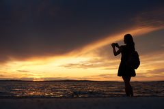 Silueta de la mujer solamente en el borde del agua, disfrutando de paisaje marino hermoso en la puesta del sol foto de archivo libre de regalías