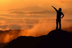 Silueta de la mujer turística que se coloca y que señala en la montaña Imagenes de archivo