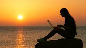Silueta de la mujer usando el ordenador portátil en la puesta del sol