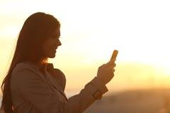 Silueta de la mujer usando un teléfono elegante en la puesta del sol Imagenes de archivo