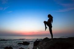 Silueta de la mujer de la yoga o de la aptitud en el mar durante puesta del sol asombrosa imagen de archivo