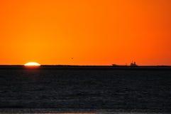 Silueta de la nave contra puesta del sol Fotos de archivo