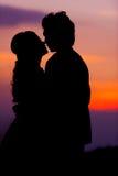 Silueta de la novia y del novio asiáticos de abarcamiento en la puesta del sol Foto de archivo libre de regalías