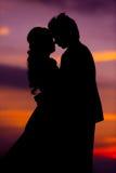 Silueta de la novia y del novio asiáticos de abarcamiento en la puesta del sol Imagen de archivo libre de regalías