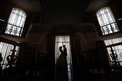 Silueta de la novia y del novio en el interior contra la ventana fotos de archivo libres de regalías