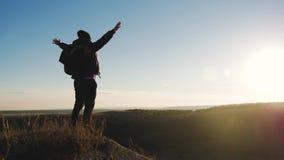 Silueta de la persona en montaña Hombre joven con la mochila que se coloca con las manos aumentadas encima de una montaña Deporte almacen de video