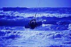 Silueta de la persona que practica surf de la cometa en fondo del cielo azul Fotografía de archivo libre de regalías