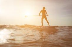 Silueta de la persona que practica surf en la puesta del sol Fotos de archivo