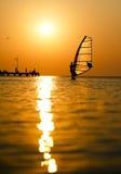 Silueta de la persona que practica surf en la puesta del sol que pasa cerca Imagenes de archivo