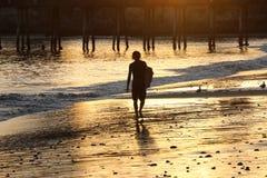 Silueta de la persona que practica surf en la playa en la puesta del sol Imagen de archivo libre de regalías