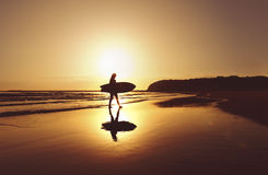 Silueta de la persona que practica surf que camina a lo largo de la playa en la salida del sol Fotografía de archivo