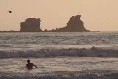 Silueta de la persona que practica surf turística que goza del mar Imágenes de archivo libres de regalías