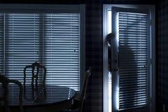 Silueta de la puerta trasera de Sneeking Up To del ladrón en la noche fotos de archivo libres de regalías