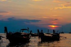 Silueta de la puesta del sol de barcos en bahía del mar Foto de archivo