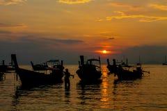 Silueta de la puesta del sol de barcos en bahía del mar Fotos de archivo