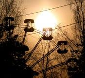 Silueta de la puesta del sol de la cabina de la noria rodeada por las ramas de árbol desnudas imagen de archivo libre de regalías