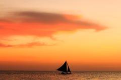Silueta de la puesta del sol del barco de navegación Fotos de archivo
