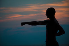 Silueta de la puesta del sol del hombre que practica artes marciales Imagen de archivo