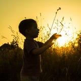 Silueta de la puesta del sol del niño Imagen de archivo