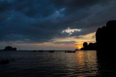 Silueta de la puesta del sol de los barcos de pesca en complejo playero del mar en Tailandia, Krabi Imagen de archivo