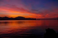 Silueta de la puesta del sol de rocas en bahía del mar Foto de archivo libre de regalías