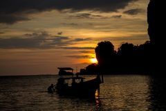 Silueta de la puesta del sol de rocas en bahía del mar Imagen de archivo