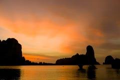Silueta de la puesta del sol de rocas en bahía en Tailandia Foto de archivo libre de regalías