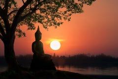 Silueta de la reflexión del agua de Buda en puesta del sol con la montaña ser imagenes de archivo