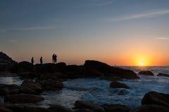 Silueta de la salida del sol que espera de la gente joven para en la roca de la orilla de mar fotos de archivo