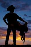 Silueta de la silla de montar de la tenencia del vaquero en la derecha de la mirada de la cadera Imagen de archivo