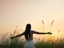 Silueta de la situación de la mujer y del brazo abierto en la puesta del sol fotos de archivo libres de regalías