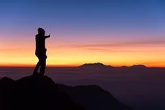 Silueta de la situación y de los pulgares del hombre para arriba en el top de la montaña Imagen de archivo