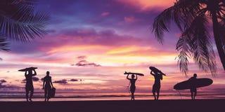 Silueta de la tabla hawaiana que lleva de la gente de la persona que practica surf fotografía de archivo libre de regalías