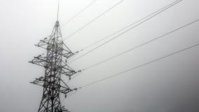 Silueta de la torre de la transmisión en fondo profundo del blanco de la niebla Imagen de archivo