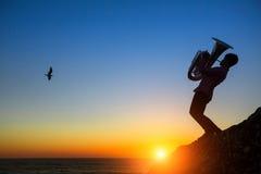 Silueta de la tuba del juego del músico en orilla de mar en la puesta del sol romance Imagen de archivo libre de regalías