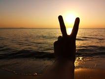 Silueta de la V-muestra del control de la mano del hombre en la playa mientras que la puesta del sol Restaure para la mañana Meta imagen de archivo