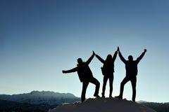 Silueta de la victoria del trío en la montaña fotos de archivo libres de regalías