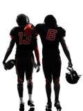Silueta de la vista posterior de dos jugadores de fútbol americano que camina Fotos de archivo libres de regalías