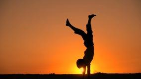 Silueta de la voltereta derecha del muchacho contra puesta del sol