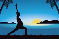Silueta de la yoga del embarazo en playa en el tiempo de la puesta del sol Fotos de archivo