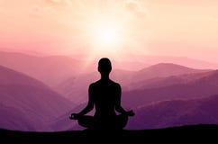 Silueta de la yoga en la montaña en rayos solares Foto de archivo