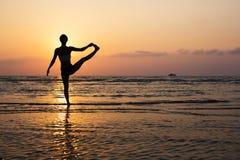 Silueta de la yoga en la playa Fotografía de archivo