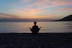 Silueta de la yoga en la playa en la puesta del sol foto de archivo libre de regalías