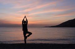 Silueta de la yoga en la playa en la puesta del sol imagenes de archivo