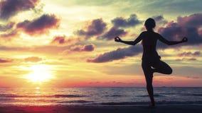 Silueta de la yoga en la puesta del sol sangrienta surrealista en la orilla de mar imagen de archivo libre de regalías